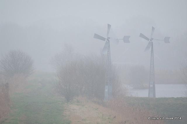 Watermolens in mistig landschap.