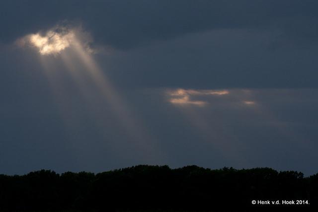 Zonnestralen vallen door een gat in de wolken.