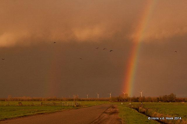 Regenboog met onheilspellende lucht er achter.