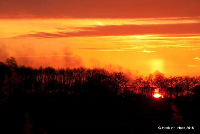 Zonsondergang op 1e paasdag met de rook van een paasvuur in beeld
